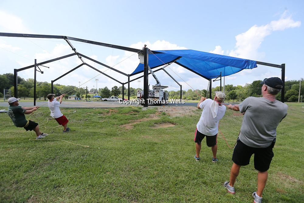 DAvid Singleton, from left, Anthony Lee, Ben Myers, Bradley Raines and Brent Williams all from Wilco Services work to secure the third corner of a new canopy being installed over the courts at Gumtree Park