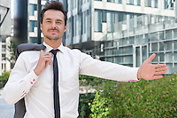 Portrait of confident businessman gesturing while standing outside office building