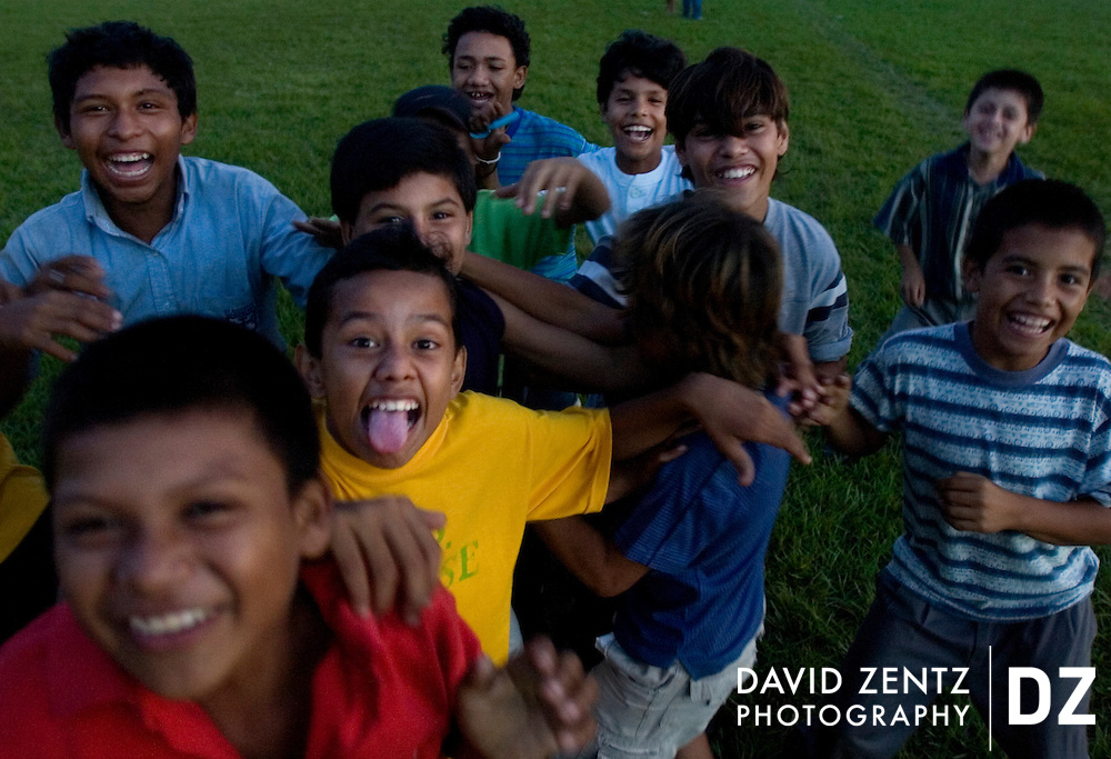 A group of young boys ham for the camera as dusk sets in at a soccer field in Jinotepe, Nicaragua on October 3, 2004.