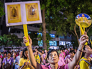 13 OCTOBER 2016 - BANGKOK, THAILAND:  A woman at Siriraj Hospital holds up pictures of the King Thursday evening after the death of Bhumibol Adulyadej, the King of Thailand, was announced. Thousands of people came to the hospital to pray for the beloved monarch. Bhumibol Adulyadej, the King of Thailand, died at Siriraj Hospital in Bangkok Wednesday, October 13, 2016. Bhumibol Adulyadej, 5 December 1927 – 13 October 2016, was the ninth monarch of Thailand from the Chakri Dynasty and is known as Rama IX. He became King on June 9, 1946 and served as King of Thailand for 70 years, 126 days. He was, at the time of his death, the world's longest-serving head of state and the longest-reigning monarch in Thai history.      PHOTO BY JACK KURTZ