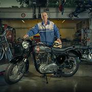"""Beroepsportret van Willem Groenewold. Hij is inmiddels al 80 maar is nog steeds een gepassioneerd restaurateur van klassieke motorfietsen. In de werkplaats van zijn zoon (Groenewold Motoren) reviseert en restaureert hij vol overgave de pareltjes van weleer. Hier staat hij bij een originele BSA, rechts achter staat zijn Royal Enfield en links op de bok staat zijn huidige project een Triumph Bonville. Willem is een geweldige kerel met enorme passie voor de motoren van vroeger waar je """"nog aan kan sleutelen in plaats van een chippie vervangen"""""""