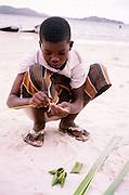 Jongetje maakt tasjes van rietbladeren