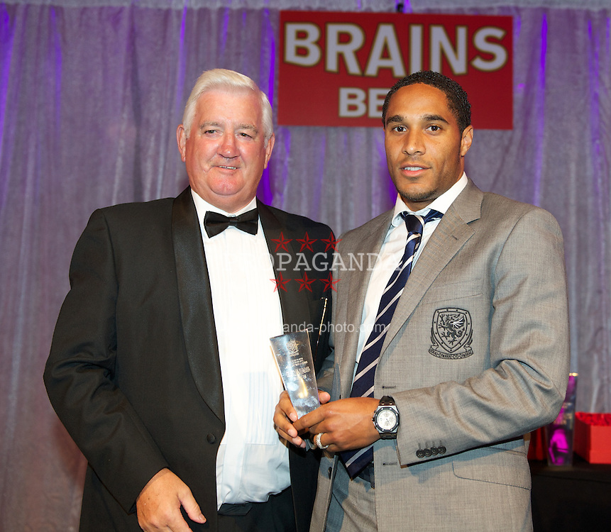 CARDIFF, WALES - Tuesday, October 4, 2011: Wales' Ashley Williams receives his Club Player of the Year Award from FAW President Phil Pritchard at the FAW Footballer of the Year Awards 2011 held at the Wales National Museum. (Pic by David Rawcliffe/Propaganda)