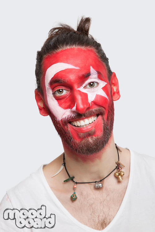 Portrait of happy young man with Turkish flag painted on face against white background