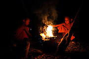 Novice Cambodian Buddhist monks light a fire at their residence in the Monks Community Forest.