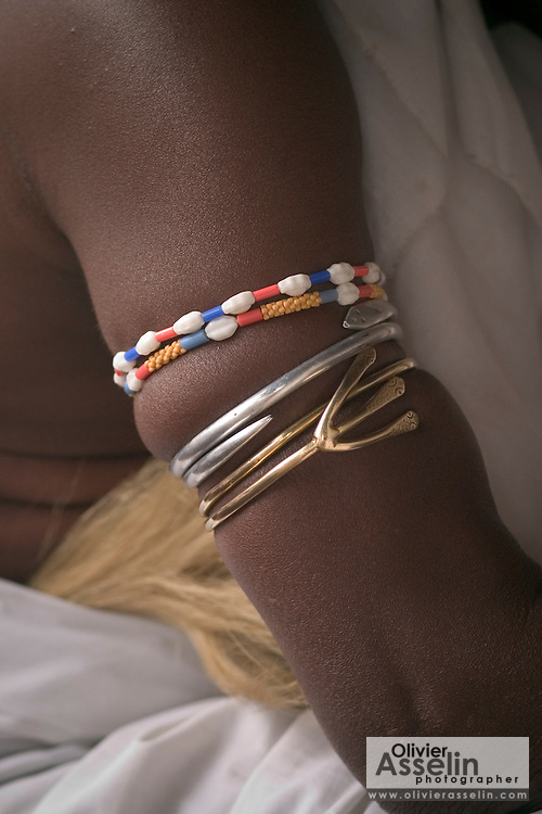 "Arm bracelets worn by the head priest during a ""coming out"" ceremony at a fetish shrine in Aflao, Volta Region, Eastern Ghana. A woman was released after spending three months in a small, dark room, hoping that she'd then be able to find a husband. Despite most Ghanaians being adamant followers of christianism or islam, many of them still maintain traditional beliefs. When facing a problem of any nature, some people will visit a local fetish shrine, looking for help. The main priest will consult the oracles and tell the person in need what has to be done for the problem to go away. People will typically be asked to ""serve"" the shrine for weeks, sometimes months, as their families pay the priest for their upkeep."