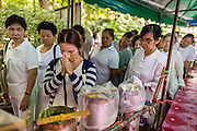11 JULY 2014 - BANGKOK, THAILAND: A woman prays after pouring molten wax into a candle mold at Wat Pathum Wanaram for Asalha Puja Day. Making candles is a traditional way of making merit before the Rains Retreat because candles were essential in former times for both ceremonies and studying scriptures during night time. The large candles that are made and given to the temple to create illumination in the belief that such a gift will likewise illuminate the mind.  Asalha Puja is the day the Lord Buddha preached his first sermon to followers after attaining enlightenment. The day is usually celebrated by merit making and listening to a monks' sermons. It is also day before the start of the Rains Retreat, the three month period when monks stay in their temple for intense mediation and spiritual renewal.    PHOTO BY JACK KURTZ