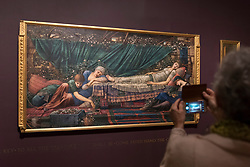 "© Licensed to London News Pictures. 22/10/2018. LONDON, UK. A visitor photographs ""The Rose Bower"", 1886-90, part of the Briar Rose series, by Edward Burne-Jones.  Preview of the largest Edward Burne-Jones retrospective to be held in a generation at Tate Britain.  Burne-Jones was a pioneer of the symbolist movement and the only Pre-Raphaelite to achieve world-wide recognition in his lifetime.  The exhibition runs 24 October to 24 February 2019.  Photo credit: Stephen Chung/LNP"