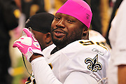 "New Orleans Saints  REMI AYODELE DT 92, gets some oxygen and show off ihs pink gloves nad scull cap during the Saints game against the Carolina Panthers Sunday Oct. 3,2010.The NFL has gone ""Pink"" for October in honor of Breast Cancer Awareness. The Saints went on to win 16-14. John Carney kicked three field goals to help the Saints win. PHOTO©SuziAltman.comIn honor of Breast Cancer Awareness month the NFL is going pink, pink gloves, pink hats, pink shoes and New Orleans Saints QG Drew Brees is pictured in front of the Making Strides Against Breast Cancer banner in the Super Dome Sunday Oct. 3,2010. SAINTS WIN 16-14 Carney kicked three field goals. PHOTO©SuziAltman.com"