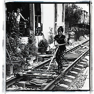 Woman pushing a strange invention that allow her to carry stuff on the railway. She looks worried and thoughtful.