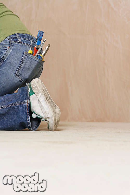 Woman with paintbrush and hand tools in back jeans pocket kneeling on floor low section