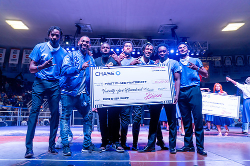 Members of Phi Beta Sigma Fraternity, the winners of Greek Step Show, holding a large check for twenty-five hundred dollars.