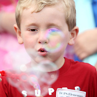 """Jace Eli Bond, 4, blows buddles during his Make-A-Wish dream on Wednesday morning at TCPS in Tupelo. Jace, a fan of the Disney Pixar movie """"Cars"""", got a car show form the Tupelo Car Club and a scavenger hunt."""
