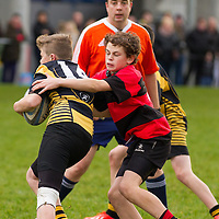 Ennis Captain Tony Butler tackles a young munster player