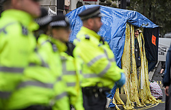 © Licensed to London News Pictures. 08/10/2019. London, UK. An Extinction Rebellion activists takes shelter in a temporary tent structure outside Home Office in Westminster. Activists have converged on Westminster for a second day, blockading roads in the area and calling on government departments to 'Tell the Truth' about what they are doing to tackle the Emergency. Photo credit: Ben Cawthra/LNP