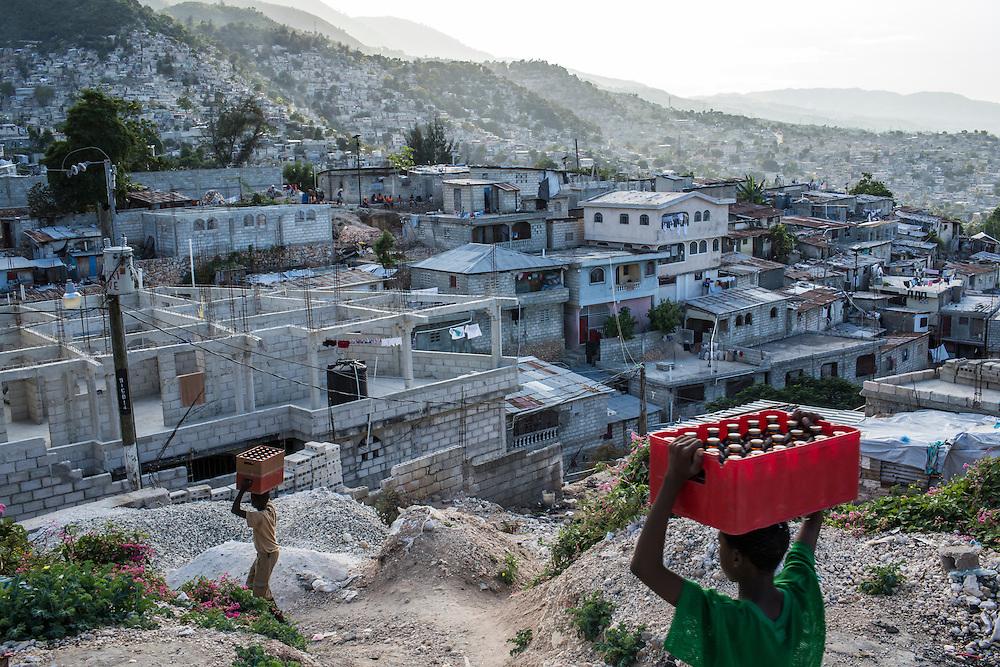 Boys carry soda bottles in the Tapis Rouge neighborhood on Friday, December 19, 2014 in Port-au-Prince, Haiti.