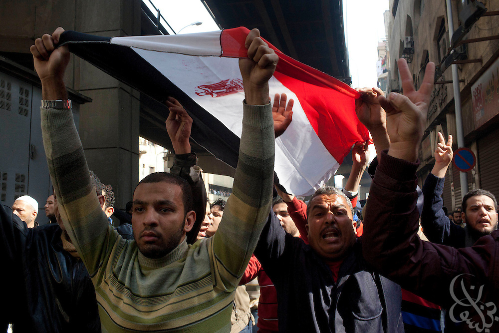 Egyptian protesters carry an egyptian flag down Al-Azhar street during massive and unprecedented demonstrations January 28, 2011 across Cairo, Egypt . The protests, inspired by the recent revolution in Tunisia, have struck a chord with Egypt's population, tired of inflation, high unemployment and alleged corruption within the Mubarak government..Slug: Egypt.Credit: Scott Nelson for the New York Times