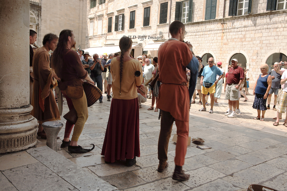 Four singers and players, one woman and three men, play on Renaissance replica instruments, wearing Renaissance era clothing.  They are seen from the back, in the shadow of a colonnade, while tourists in shorts watch and listen in the sunshine beyond.
