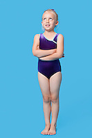 Young female gymnast with arms crossed looking up over blue background