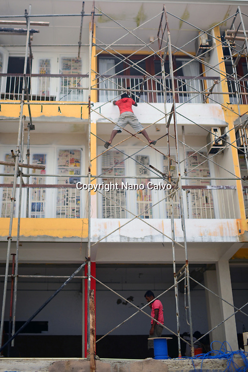 Construction worker exemplifies the concept of occupational hazard while working on a high scaffold, Sri Lanka