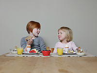 Sisters sit eating breakfast together and talking