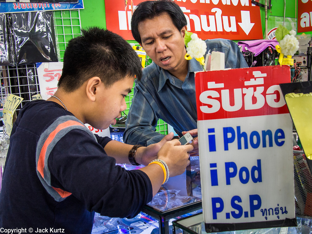 21 SEPTEMBER 2013 - BANGKOK, THAILAND: A man looks at an iPhone 5s in an electronics shop in MBK in Bangkok. Customers around the world lined up Friday to pick up Apple's new flagship iPhone 5s and its lower cost, more colorful brother, the iPhone 5c. The phones went on sale in the US and select countries beyond the US on Friday. The iPhone 5s and iPhone 5c will not be officially released in Thailand until late 2013 but the phones are available through the unofficial grey market in MBK, a huge shopping complex in Bangkok with dozens of small electronics shops. Early purchasers in Thailand pay a premium for the new iPhones, the top of the line iPhone 5s with 64 gigabytes of memory is about 38,500Baht, more than $1,200 (US).      PHOTO BY JACK KURTZ