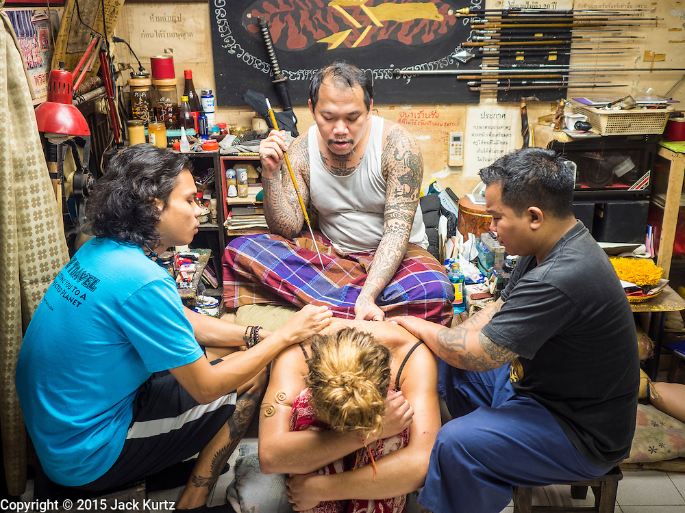 """27 MAY 2015 - BANGKOK, THAILAND: AJARN NENG ONNUT, gives a sacred Sak Yant tattoo to EMILY, a visitor to Thailand from the United Kingdom. Sak Yant (Thai for """"tattoos of mystical drawings"""" sak=tattoo, yantra=mystical drawing) tattoos are popular throughout Thailand, Cambodia, Laos and Myanmar. The tattoos are believed to impart magical powers to the people who have them. People get the tattoos to address specific needs. For example, a business person would get a tattoo to make his business successful, and a soldier would get a tattoo to help him in battle. The tattoos are blessed by monks or people who have magical powers. Ajarn Neng, a revered tattoo master in Bangkok, uses stainless steel needles to tattoo, other tattoo masters use bamboo needles. The tattoos are growing in popularity with tourists, but Thai religious leaders try to discourage tattoo masters from giving tourists tattoos for ornamental reasons.     PHOTO BY JACK KURTZ"""