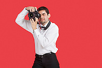 Mixed race man taking picture with digital camera over red background
