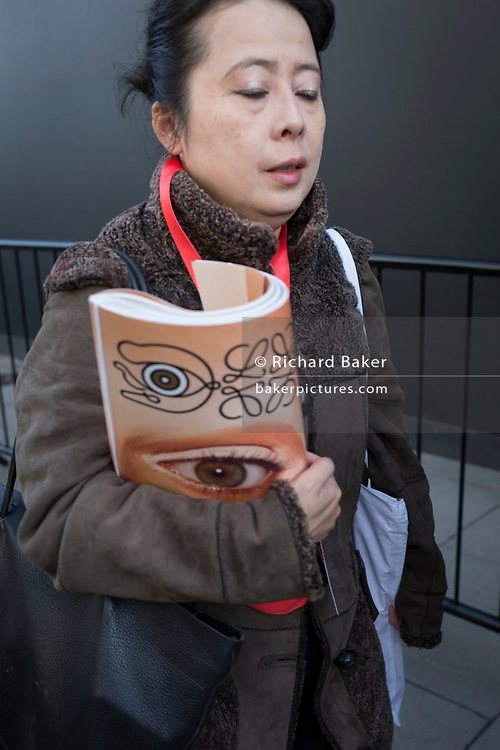 A women with eyes closed walks carrying a free magazine featuring an eye on the cover on the first day of London Fashion Week in the Strand, on 16th february 2018, in London, England,