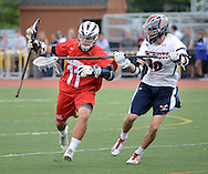 DOYLESTOWN, PA - MAY 15: Holy Ghost Prep's Bennett Zaba #11 stick handles the ball as he is hit in the face with a stick by Central Bucks East's Dustin Buchanan #16 in the first half May 15 2014 at War Memorial Field in Doylestown, Pennsylvania. (Photo by William Thomas Cain/Cain Images)