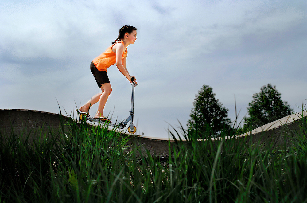 Hallie Wilt, 8, zips over concrete waves in the early-morning heat. Yesterday, rain delayed her older sister's softball games. The wet ground has delayed them again this morning, but the sun has dried the concrete of Columbia Skate Park inside Cosmo Park.<br /> <br /> Hallie and her younger sister Carlee, 7, are off and running, scooters coasting in lazy figure eights, their father, James, watching from a seat in the shade.<br /> <br /> Sisters have to stick together in times of boredom. After hours of braiding hair and playing computer games under a tent, the girls are happy to be out in the sunshine.<br /> <br /> Hallie walks to the top of a short ramp and grips her handlebars tight. There's no pushing off, just a slow acceleration as she catches speed on the downhill. Halfway up the opposite ramp, her momentum gives out. She hops off and walks the rest of the way.<br /> <br /> &quot;The first time we came to ride, we were scared,&quot; Hallie says. &quot;The ramps make you go pretty fast.&quot;<br /> <br /> &quot;And I fell on the water and skinned my knee,&quot; Carlee adds, pointing down to the scratched skin and mud on her left leg.<br /> <br /> &quot;But we're better today,&quot; Hallie clarifies.<br /> <br /> After an hour, the heat has flushed their cheeks and dried the softball fields. Their father calls them in.<br /> <br /> They call to each other from opposite sides of the park and come together for one last run down the small ramp, their matching French-braid pigtails trailing behind.