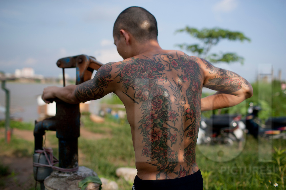 A tattooed man pumping water by hand, beside the Red River, Hanoi, Vietnam, Southeast Asia