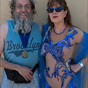 23rd Mermaid Parade, three quarter length colorful portrait of couple  wearing colorful costumes before the start of the parade in Coney Island.<br /> <br /> He is a two time winner of the Neptune metal award, going for his three time.