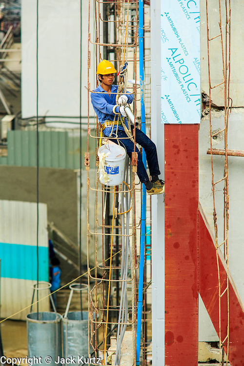16 OCTOBER 2012 - BANGKOK, THAILAND: A worker on scaffolding seals a seam in a concrete wall at a residential condominium project on Th Phaya Thai near the intersection with Phetchaburi Rd. in Bangkok. The global economic slowdown had little visible effect in Bangkok. Construction projects dot the city of 12 million and development continues unabated.    PHOTO BY JACK KURTZ