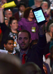 """© Licensed to London News Pictures. 03/10/2012. Manchester, UK A man holds up a tablet computer saying """"pick me please ed' as Ed Miliband takes part in a question and answer session on Day 4 at The Labour Party Conference at Manchester Central today 3rd october 2012. Photo credit : Stephen Simpson/LNP"""