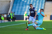 Queens Park Rangers forward Jordan Hugill (9) fouls Millwall midfielder Jed Wallace (7) by performing a sliding tackle during the EFL Sky Bet Championship match between Millwall and Queens Park Rangers at The Den, London, England on 21 September 2019.