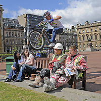 YouTube sensation Dan MacAskill  jumps between builders Debbie Grant aged 19 from Thornliebank and Heather Nicol aged 26 from St Andrew (left) and builders Maciej Swiderski(hat) and Neil McSkeane (right) who were taking a break from working on the old Post office building in George Square.  Dan was launching Bike Week in George Square.