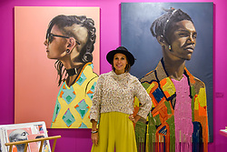 "© Licensed to London News Pictures. 05/10/2019. LONDON, UK. Artist Athena Anastasiou poses with two of her works (L to R) ""The Modern Muisca"", 2019, and ""Bringing the Past to New Horizons"", 2019, at The Other Art Fair, presented by Saatchi Art.  120 international, independent artists are displaying their works to be sold direct to buyers.  The fair is taking place at Victoria House in Bloomsbury until 6 October 2019.  Photo credit: Stephen Chung/LNP"