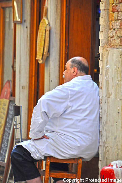 Study of a man sitting on a chair in a Venetian alleyway.