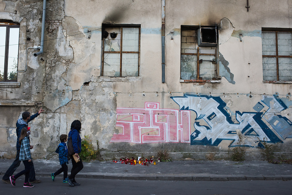 People pass by the exterior of the Colectiv nightclub, where damage from the fire that killed 41 people so far, on November 8, 2015 in Bucharest, Romania. Damage from the fire can be seen at the top of two of the windows.