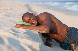 Young man leaning on a beach sand bank smiling