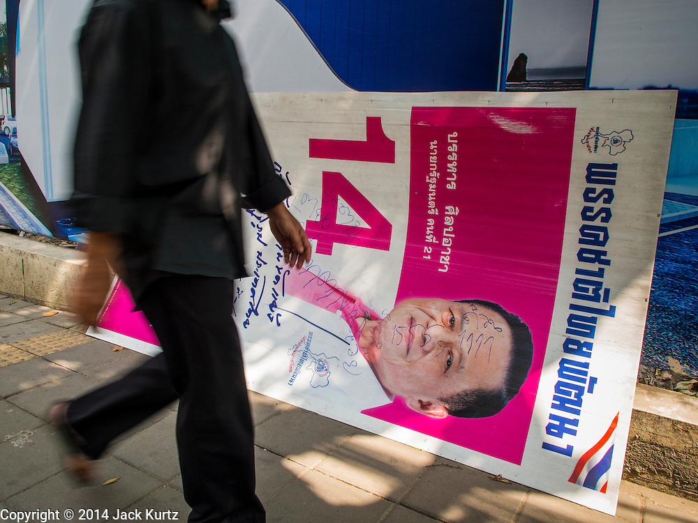 29 JANUARY 2014 - BANGKOK, THAILAND:  A person walks past a defaced campaign sign on a Bangkok street. Thais are supposed to vote Sunday, February 2 in a controversial national election. Anti-government protestors have vowed to disrupt the election. One person was killed and several injured in election related violence during early voting on Sunday Jan. 25. The ruling Pheu Thai party is widely expected to win the election, which is being boycotted by the Democrats and opposition parties.      PHOTO BY JACK KURTZ