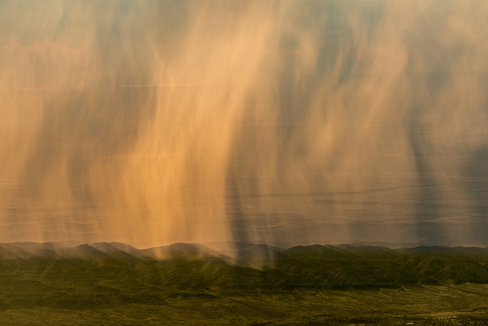 Bands of rain, falling above Oregon's Alvord Desert at sunrise, hide the landscape behind a semi-transparent veil.