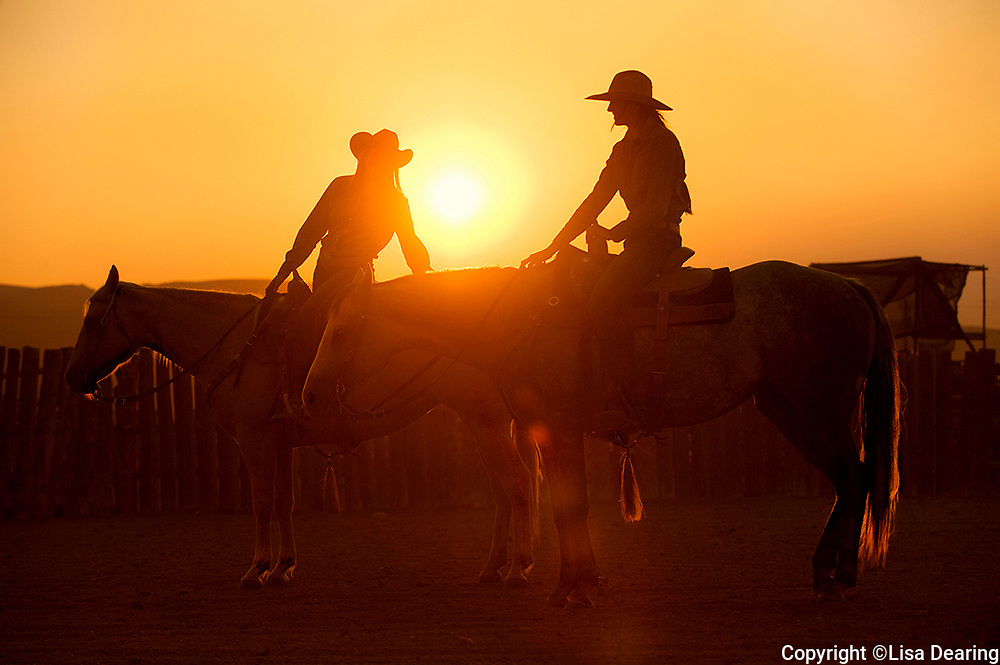 Two Idaho Cowgirls on Horses in Round Pen at Sunset