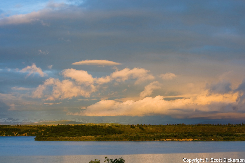 Whisping clouds, snowy mountains and lush tundra surround the Naknek River in Bristol Bay, Alaska at sunset.
