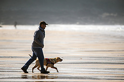 A man and his dog enjoy a brisk walk on Fistral Beach in Newquay, Cornwall.