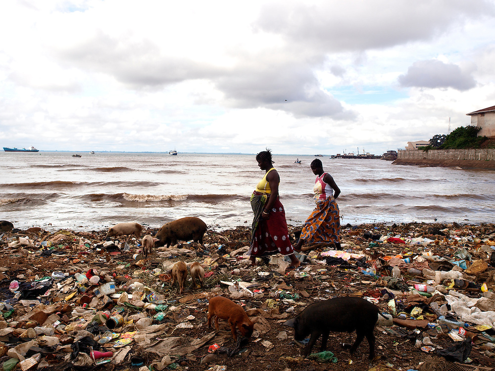 Two pregnant ladies walk through the garbage in the slum they live in. ..Kroo Bay, Freetown, Sierra Leone.