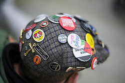 © Licensed to London News Pictures. 04/10/2017. Manchester, UK.  Badges on the cap of one of the DPAC protesters during the demonstration on the final day of the Tory Party Conference. The protest was as part of the Take Back Manchester festival to protest the conference taking part in the city.  Photo credit: Steven Speed/LNP