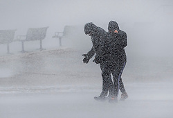 © Licensed to London News Pictures. 09/02/2020. Portsmouth, UK. A couple get a soaking from the waves at high tide on the sea front at Southsea, Portsmouth as Storm Ciara batters the UK. Airlines have cancelled dozens of domestic and international flights as the storm brings strong winds and rain. Photo credit: Peter Macdiarmid/LNP
