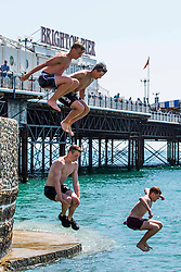 © Licensed to London News Pictures. 14/07/2016. Brighton, UK. Daredevils jump of the pontoon into the sea to cool down while thousands of visitors take the beach in Brighton and Hove as sunny and hot weather continues to hit the seaside resort. Photo credit: Hugo Michiels/LNP